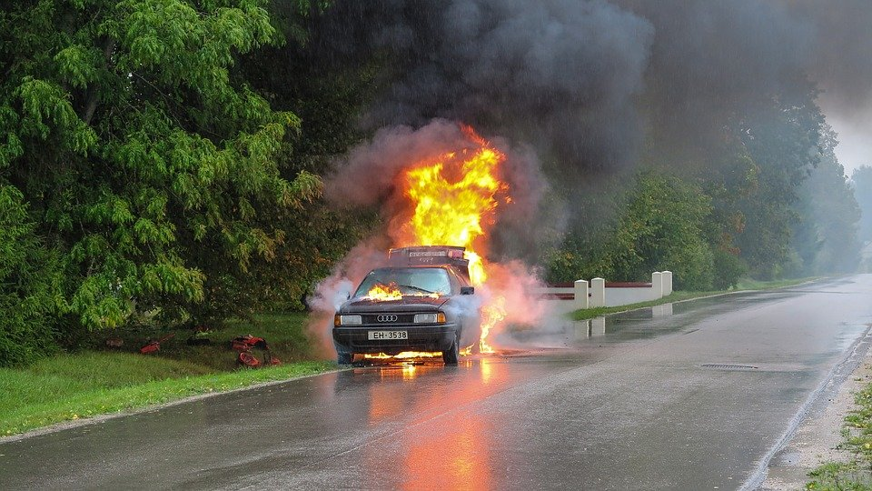 горящий автомобиль на обочине дороги