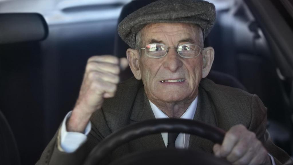 Пожилой мужчина за рулем