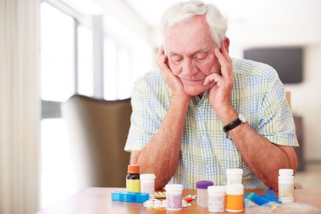Пожилой мужчина с лекарствами